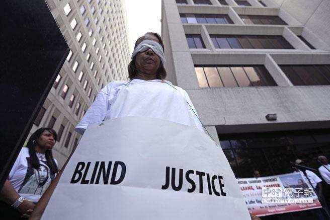 佛羅里達州西語裔白人守望互助隊員辛默曼(George Zimmerman)涉嫌槍殺無武裝非洲裔少年馬丁(Trayvon Martin)背叛無罪,引發全美各地抗議,圖為抗議者手持盲目正義的標語!﹝美聯社﹞