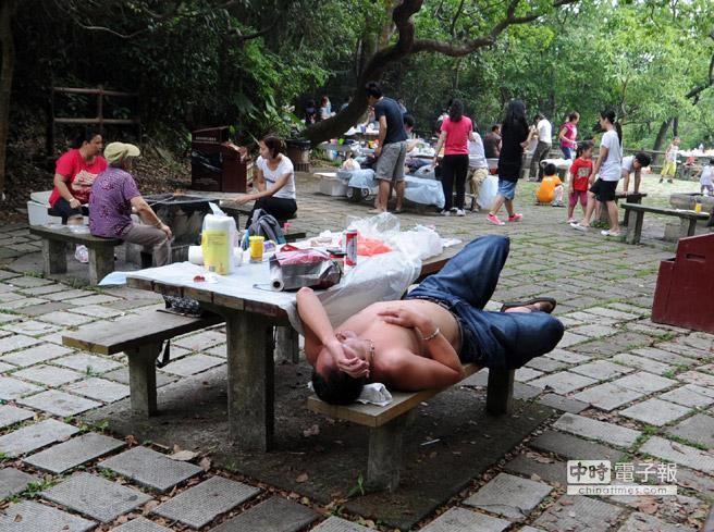 圖為一位膀爺難耐高溫,在公園赤膊納涼小憩。﹝香港中通社﹞