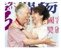張金松(左起)今年獲頒「客家貢獻獎」傑出成就獎殊榮,她的女兒上台擁抱恭喜他。(本報資料照片/陳志源攝)