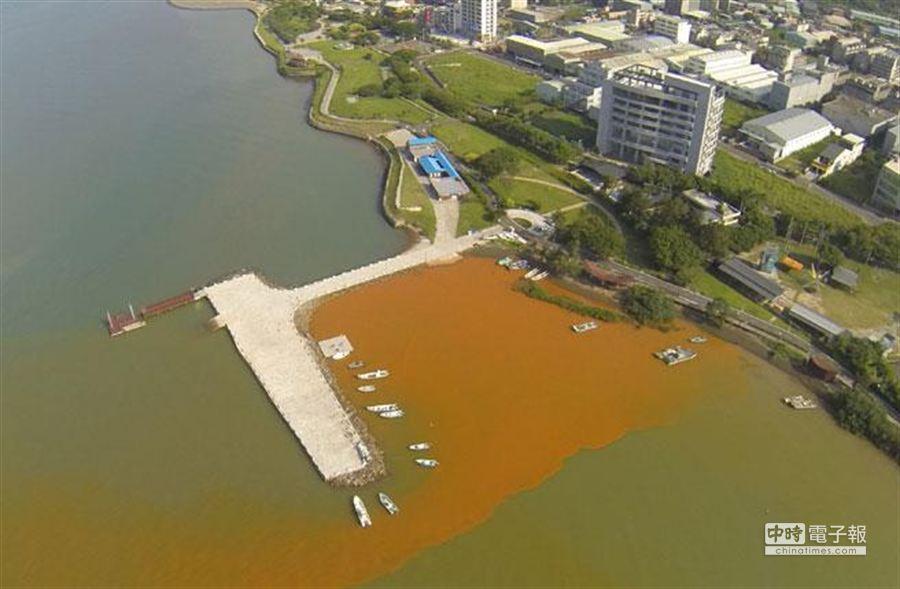 八里風帆碼頭的空拍圖,工廠所排出的紅色廢水讓淡水河左右岸呈現「陰陽海」的情況。(新北市環保局提供)