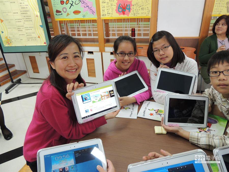 北市教師自製兒童英語圖書,APP首度提供免費下載,北市教育局長林奕華(左)與三玉國小學童一起使用平板電腦現場操作使用。(石文南攝)