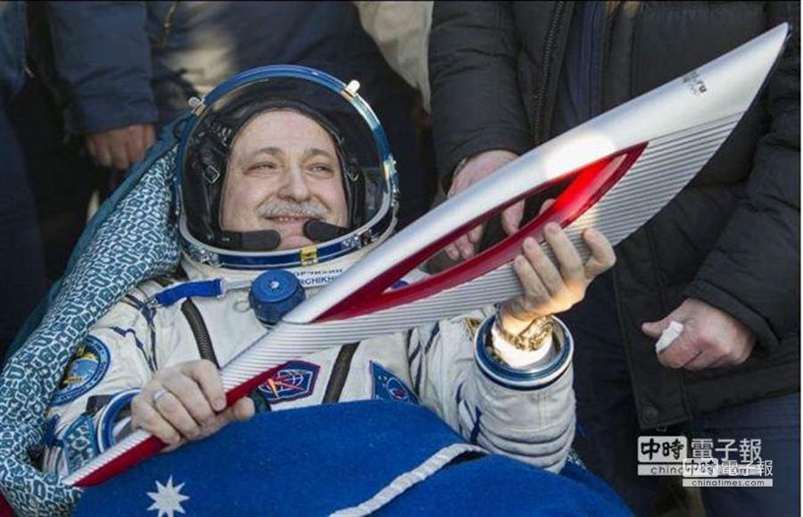 支持冬季奧運,俄羅斯太空人Fyodor Yurchikhin手持聖火,平安返回地球。(美聯社)