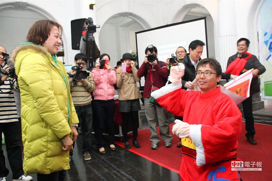 扮財神爺的TVBS記者陳世明拿出1個「大鑽石」,向任職新竹市政府影音小組的女友羅欣怡下跪求婚。(羅浚濱攝)