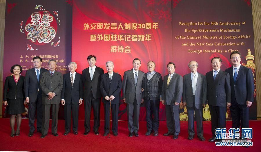 2013年12月12日,中國外交部發言人制度30周年暨外國駐華記者新年招待會,在北京大都美術館舉行。圖為外長王毅在招待會上同新老發言人合影。(新華網)