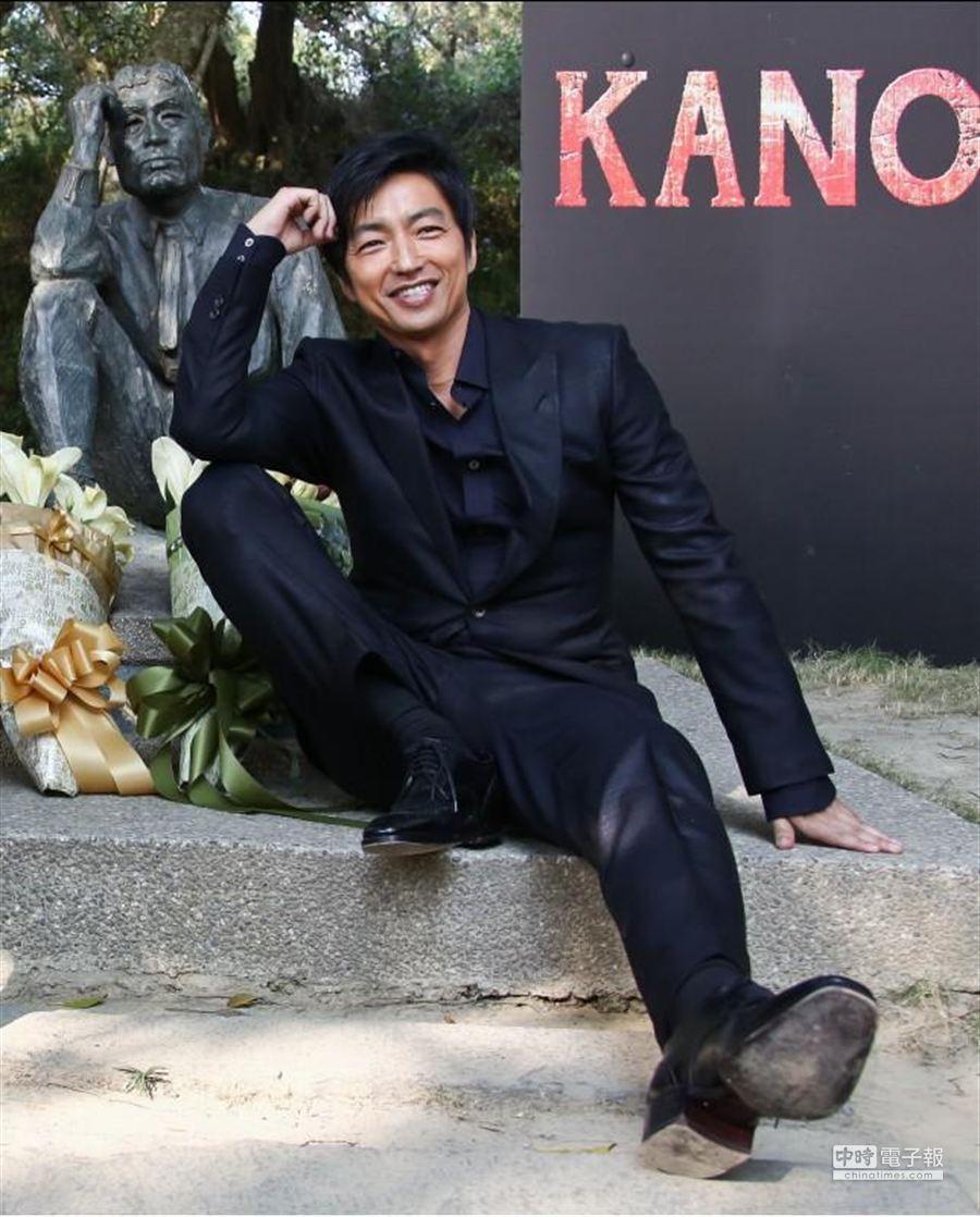 大澤隆夫模仿八田與一雕像的坐姿。(羅永銘攝)