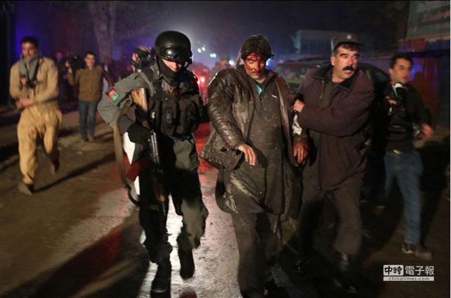 喀布爾使館區餐廳爆炸案,造成死傷慘重,一名滿臉是血的受害人在旁人扶持下,驚慌逃離現場。(美聯社)