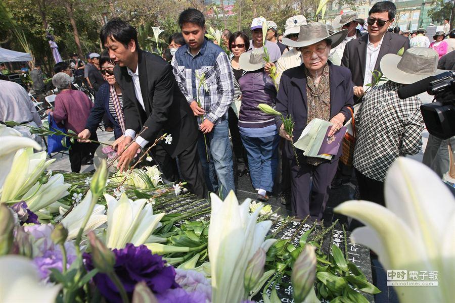 高雄市228事件67週年追思儀式,在228和平紀念公園舉行,追思儀式上受難者家屬共同在紀念碑前獻花。(謝明祚攝)