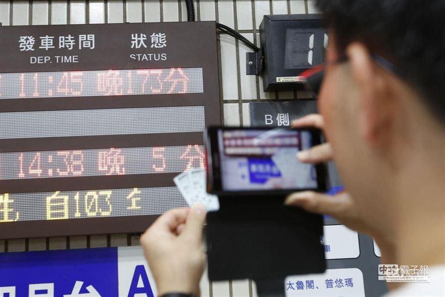 民眾自拍火車票與誤點173分鐘告示牌。(圖/陳振堂攝)
