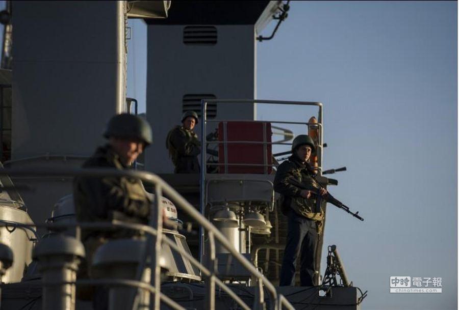烏克蘭海軍3日在司令艦「斯拉夫蒂奇號」上持槍站崗。俄方表示,所謂最後通牒一事係子虛烏有。(美聯社)