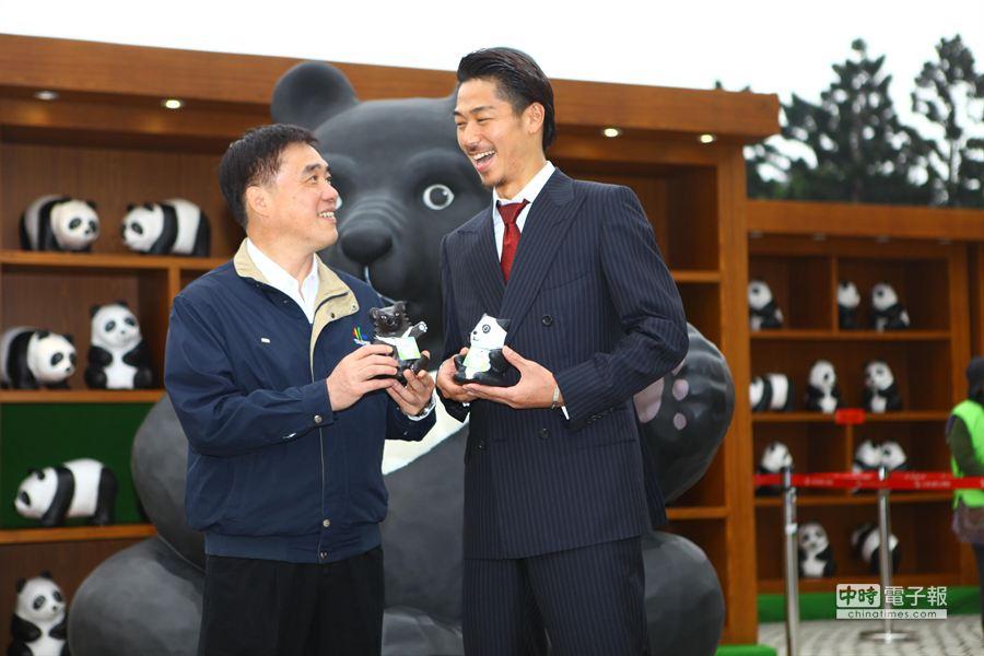 放浪兄弟團員AKIRA(右)受邀看紙貓熊展,台北市長郝龍斌(左)贈送紙雕貓熊和紙雕台灣黑熊。(張立勳攝)