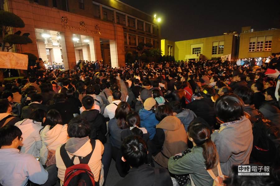 上百位學生及民眾23日晚間翻過行政院的鐵柵欄,搬開拒馬,就地坐在行政院的廣場,攻占行政院。(劉宗龍攝)