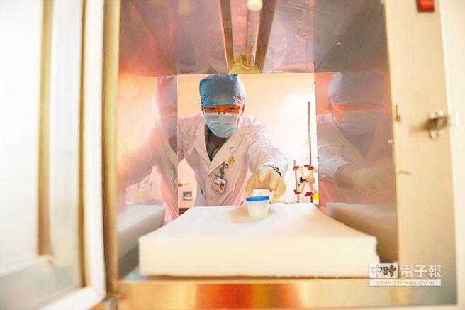 圖為大陸某精子庫,工作人員在取精液樣本。(中新社)