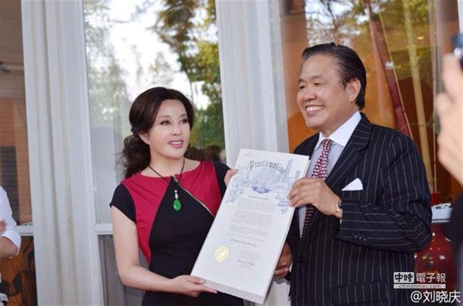 劉曉慶(左)從美南新聞電視報業集團董事手中接獲休斯頓市長頒發獎狀。(取材自劉曉慶微博)