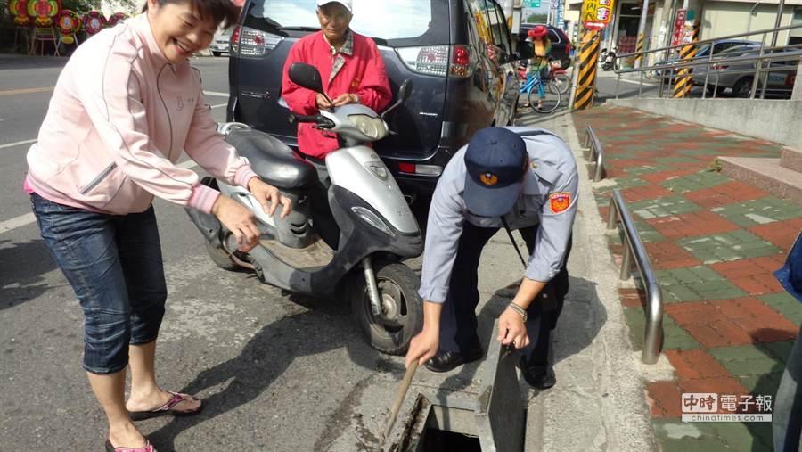 員警陳永富翻開水溝蓋,幫婦人找到印章。(許素惠攝)