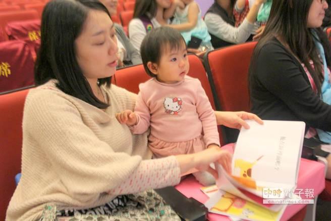 小孩觀看紀錄片偶爾哭鬧,媽媽得拿出故事書吸引注意力。(郭逸攝)