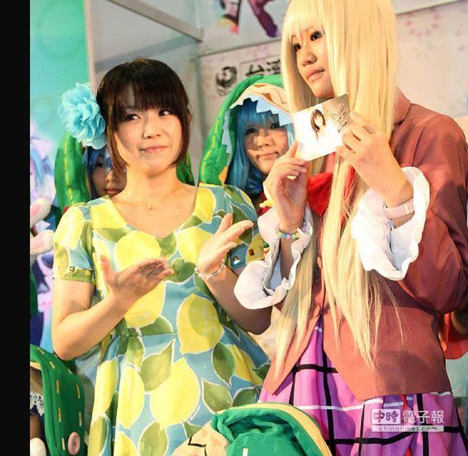 2013漫畫博覽會,台灣角川請來《約會大作戰》動畫聲優野水伊織(左)舉行簽名會,活動開始前和精心打扮的COSPLAY粉絲合影留念並送上自己的簽名照。(資料照片 趙雙傑攝)