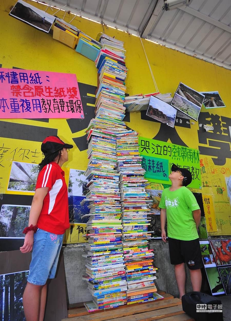 小朋友觀看用國中與高中的課本、補充教材等書本堆疊而成的「書樹」。(劉宗龍攝)