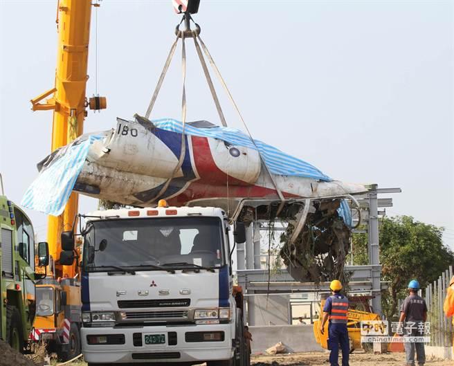 軍方人員將墜落的飛機機身殘骸吊掛上拖車準備拖離。(謝明祚攝)
