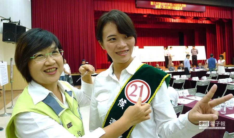 市議員徐佳青為接棒參選的簡舒培貼上號次。(江慧珺攝)