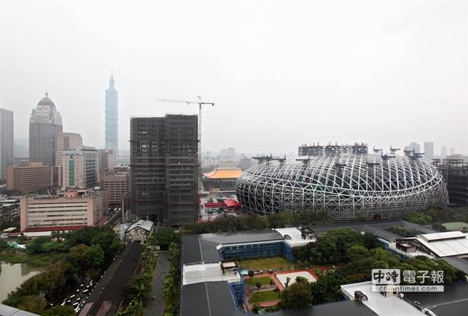 台北遠雄巨蛋13日舉行屋頂提升暨上樑典禮,展示全球罕見提升工法,1次將  4600噸的巨蛋屋頂「提起來」至地面62公尺高定位,將來巨蛋球場位置在地下2樓,總高度將為72公尺。  台北遠雄巨蛋是全球第1大跨距非對稱提升工法首例,室內跨距長寬230 M x 170 M,也是全球唯一整個巨  蛋全採圓型鋼管,45度角焊接工程,鋼構總量為65000噸。園區10.2公頃,約30250坪,含松菸共18公頃,  預計2016年中試營運。圖為位在松菸文創園區及國父紀念館之間的台北大巨蛋。圖為位在松菸文創園區  及國父紀念館之間的台北大巨蛋,一旁是台北101大樓及遠雄總部(左)。(王錦河攝)