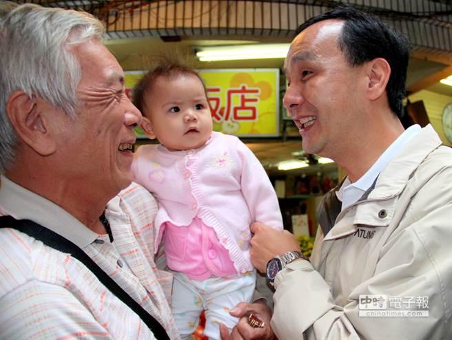 阿公試圖讓孫女與朱立倫握手,但孫女一臉疑惑。(謝文瑄攝)