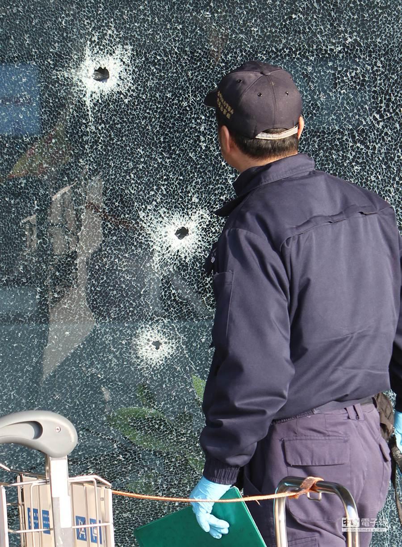 台中清泉崗機場19日下午發生警匪槍戰,機場大廳玻璃帷幕彈痕累累,一名警方鑑識人員,趨前查看。(黃國峰攝)