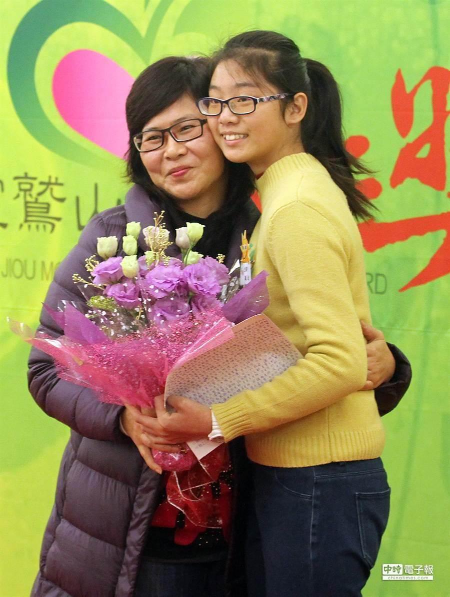 獲獎的民生國中學生吳佩均(右)獻花給辛苦拉拔她長大的媽媽。(趙雙傑攝)
