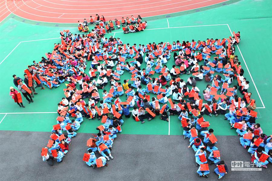 台中市大同國小400名學生拿著自己寫的春聯作品,排出喜氣洋洋的吉祥羊,迎接羊年,創意十足。(盧金足攝)
