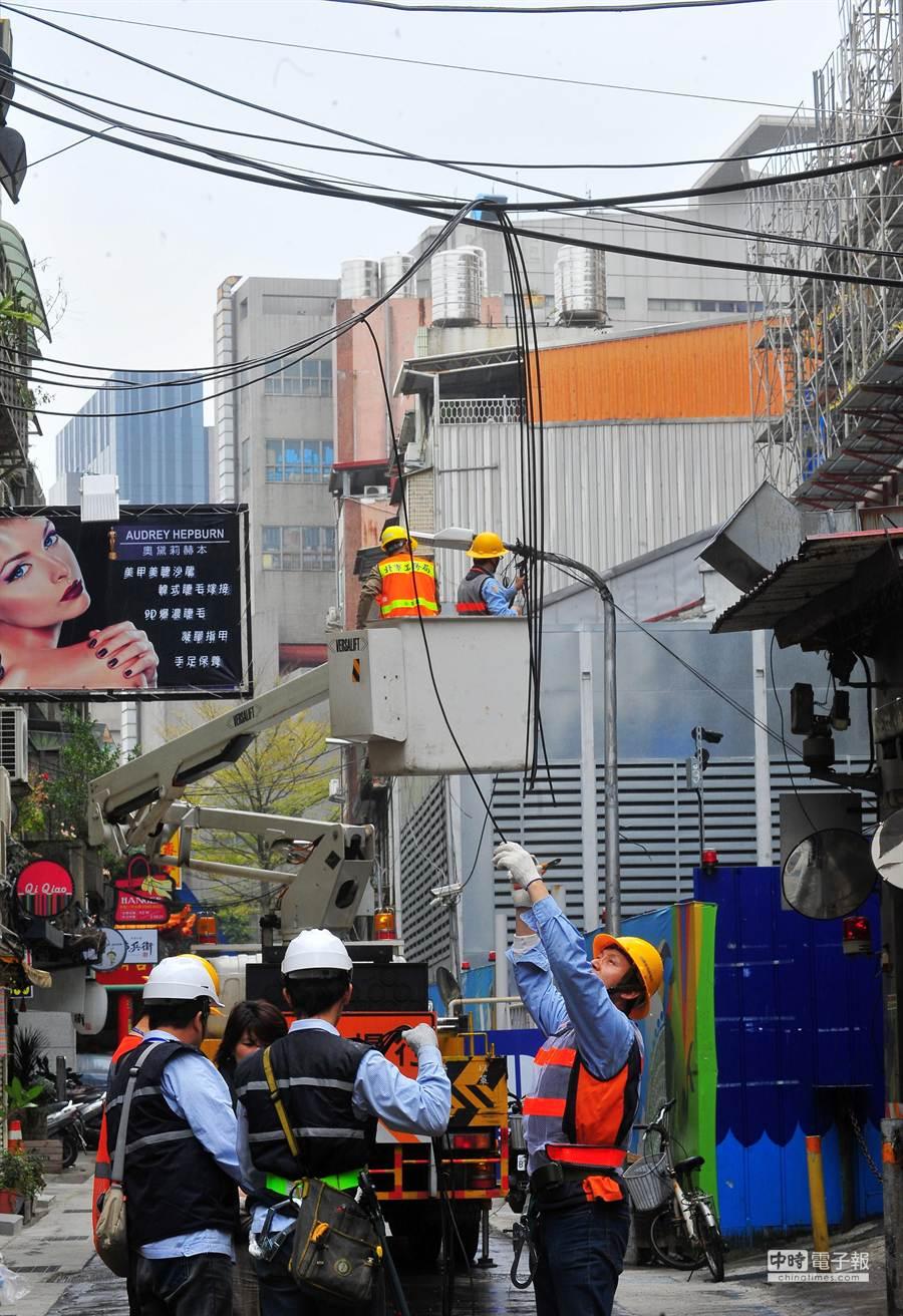 台北市工務局工程人員剪掉吊掛在半空中各種纜線,要乾淨的天空還給市民。(劉宗龍攝)