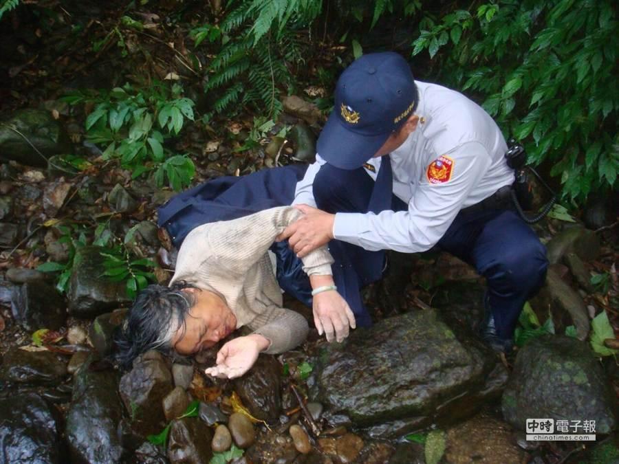 1名年約70歲的老婦人今天(29日)下午被人發現倒臥在新店山區溪谷,全身不停發抖,率先趕抵現場的派出所員警脫下警用外套蓋住她禦寒。(孟祥傑翻攝)