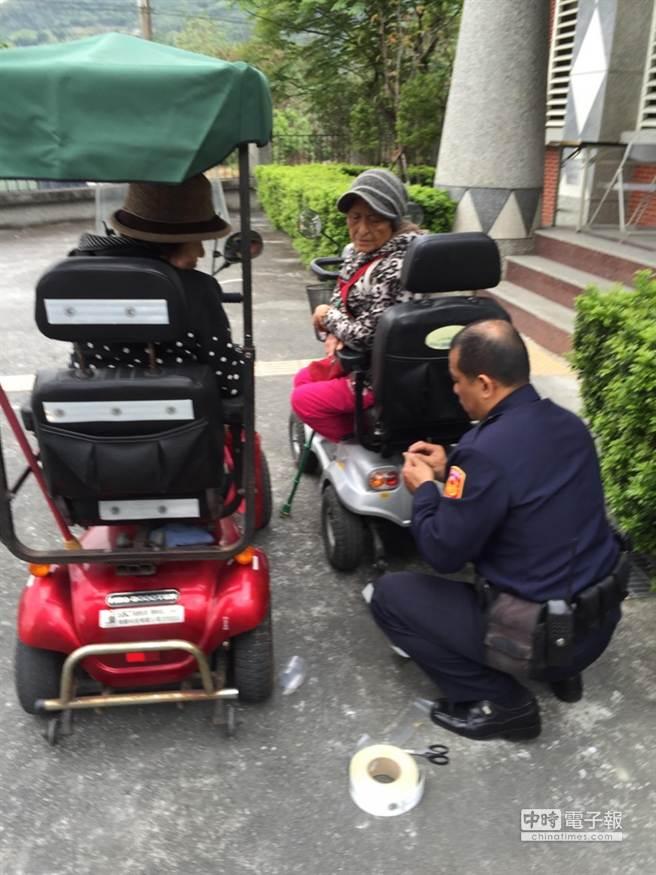 吉安警分局水源派出所長游國華(右)主動幫長者在電動車後方貼反光條,獲得好口碑。(阮迺閎翻攝)