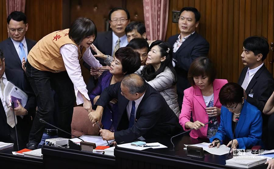 立委周倪安(左二)數度跳上桌子並拉扯麥克風。(姚志平攝)