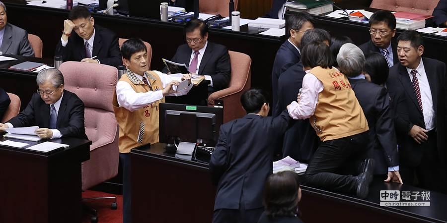 立委周倪安(右前)數度跳上桌子遭攔阻,立委賴振昌(左前二)則拿起手機拍照存證。(姚志平攝)