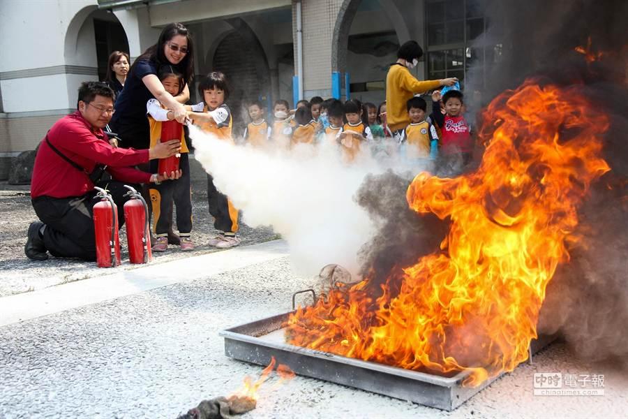 壯圍鄉立幼兒園師生在消防隊員指導下,拿起滅火器向烈焰噴灑乾粉。(簡榮輝攝)