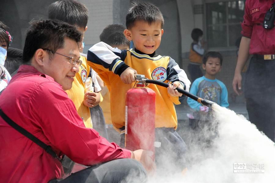 壯圍鄉立幼兒園學童在消防隊員指導下,拿起滅火器向烈焰噴灑乾粉。(簡榮輝攝)