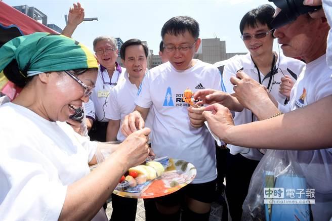 民眾熱情地拿食物給台北市長柯文哲(中)試吃。(黃世麒攝)