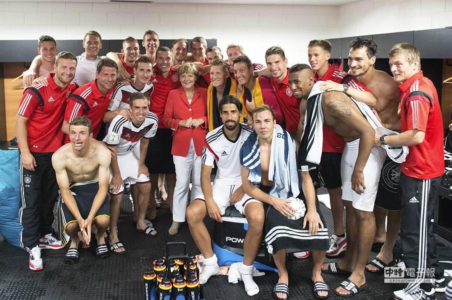 德國總理梅克爾女士(中)5連冠全球最有權力女性榜,跟2014年世界杯足球賽第5次奪冠的德國隊在休息室合照。(本報系資料照片)