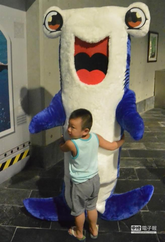 屏東海生館推出「鯊魚特展」,小朋友緊緊抱著鯊魚吉祥物,非常可愛。(潘建志攝)