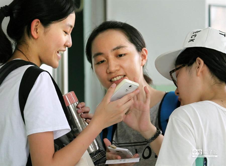 金車教育基金會30日公布學生使用手機調查結果,台灣有近8成6的學生擁有行動電話,且95%是智慧型手機。圖為幾位學生相互觀看手機訊息。(王錦河攝)