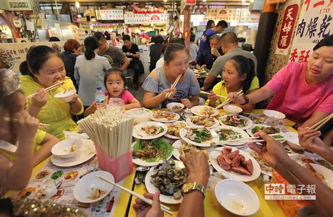 國際觀光客平均每人花費約42500台幣遊台北,名列第3名。圖為幾位從武漢初次來台旅遊的大陸觀光客一家子在士林夜市享用美食。(王錦河攝)