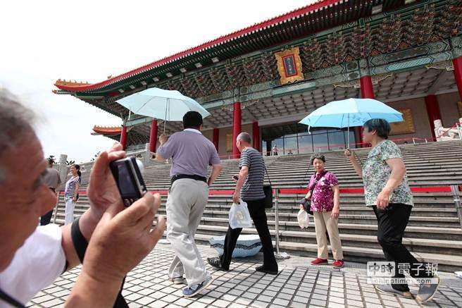 一對從山東省青島來台旅遊的夫婦正幫老伴在國家戲劇院前拍照留念。(王錦河攝)