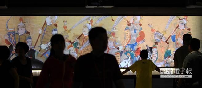 幾位觀光客在台北故宮觀賞「出警入蹕圖」古畫投影動漫。(王錦河攝)