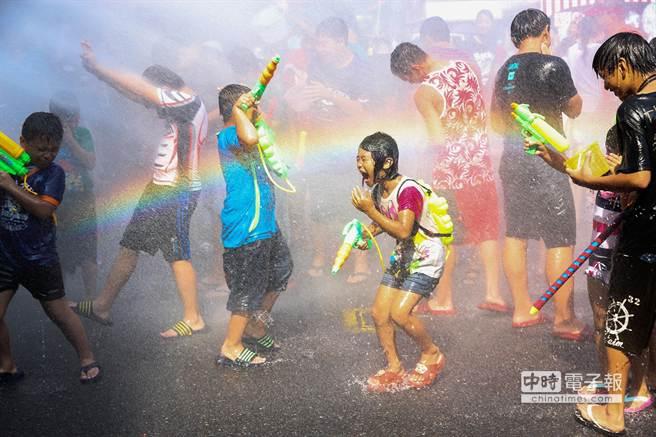 蘇澳火車站前廣場成為水仗戰場,許多揹著水槍的孩童迎向水車水柱,開心歡呼。(簡榮輝攝)