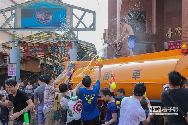 蘇澳火車站前廣場成為水仗戰場,許多原本受到水柱噴灑的人群,見到水車沒水了,紛紛拿起水槍群攻水車射手。(簡榮輝攝)