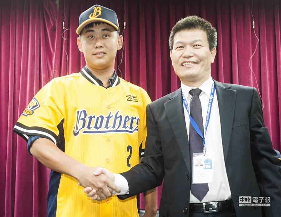 中信兄弟31日正式與5位選秀選手簽約,潘萣翔(左)在領隊楊培宏為他戴上球帽後,正式成為中信兄弟的一員。(鄭任南攝)