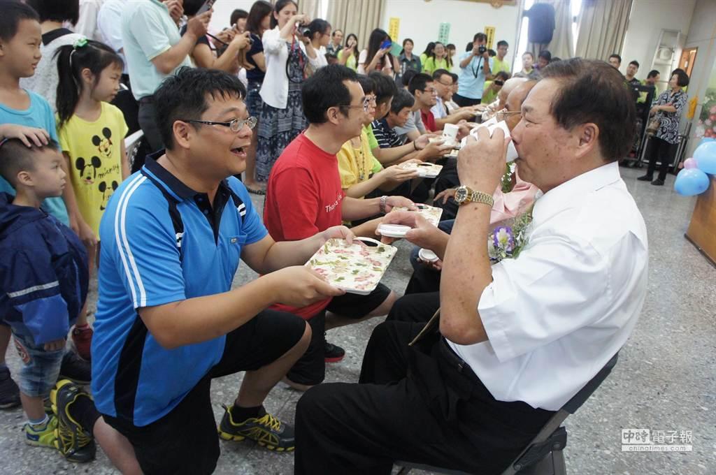 王和平的兒子恭敬跪著,張大嘴巴看老爸喝茶,王和平非常享受這杯特別好喝的茶。(周麗蘭攝)