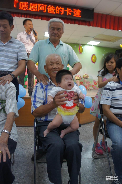 九十歲張銀生是現場最老的模範父親,手裡抱著曾孫,背後有六十三歲兒子抓龍。(周麗蘭攝)