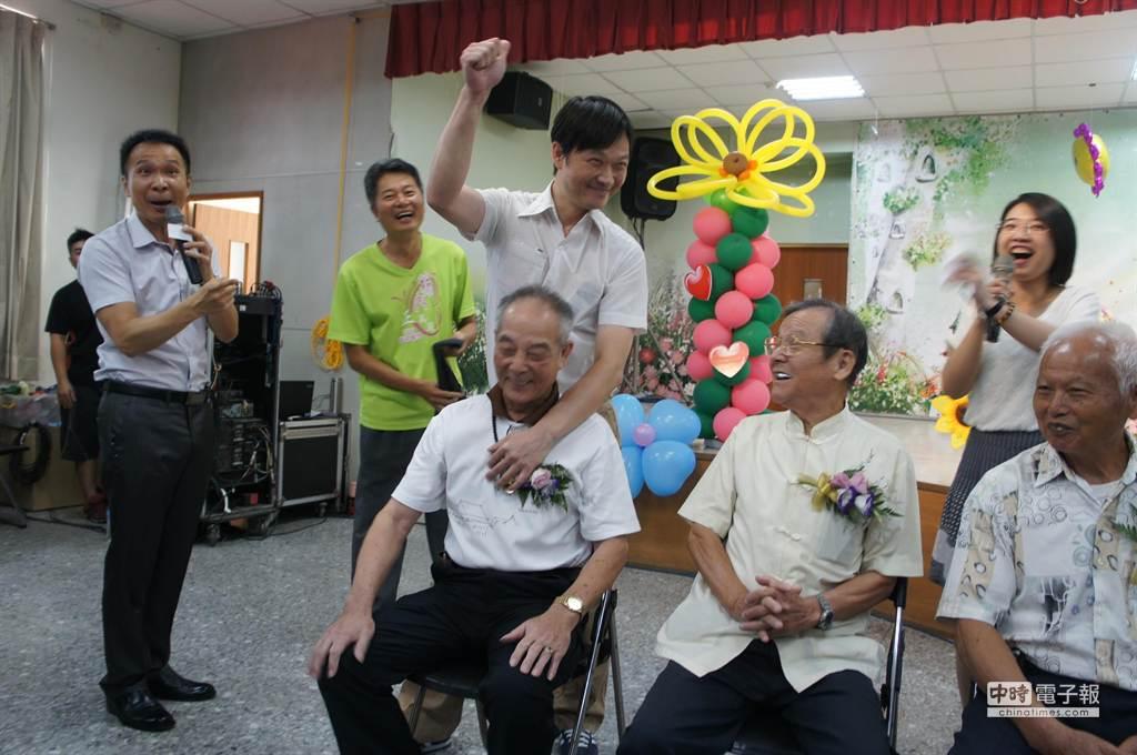 七十五歲老爸李世華,被四十五歲兒子猜中肩膀,兩人都非常開心。(周麗蘭攝)