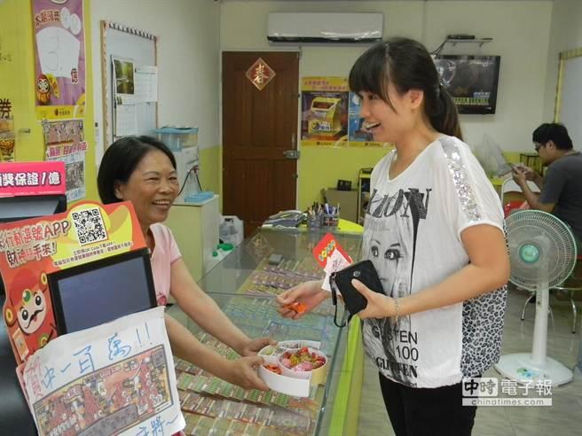 老闆娘張美惠(左一)請彩迷吃糖,分享好運。(王文吉攝)
