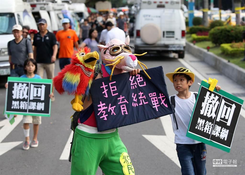 1位特殊裝扮男子在人群中格外顯目,兩位參與遊行的小朋友好奇追上一探究竟。(王錦河攝)